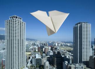 高層マンションを飛ぶ紙飛行機