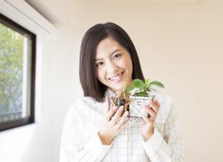 植物を持ちながら微笑む女性
